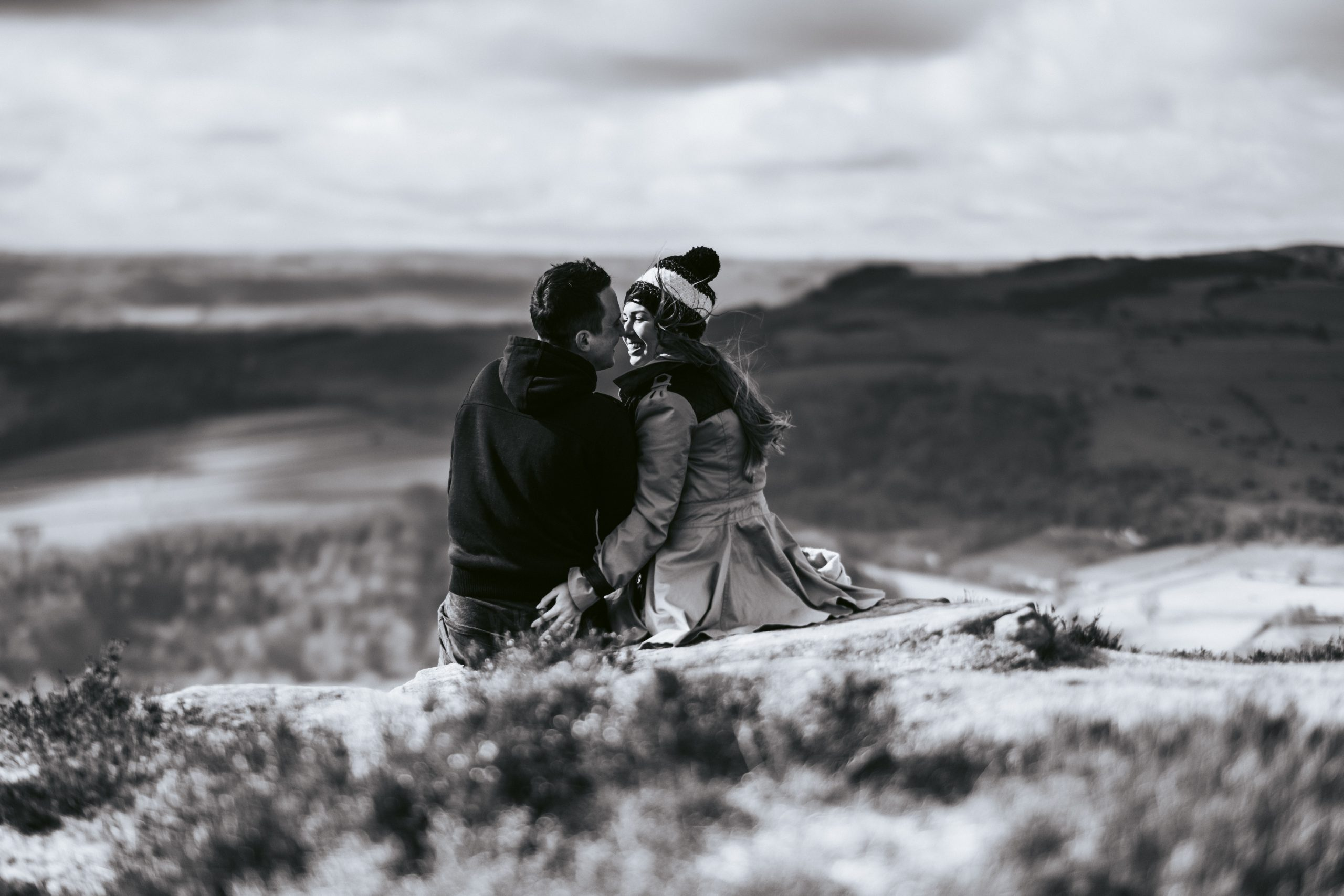 beautiful light up on dartmoor, a couple lean in for a kiss on their engagement shoot