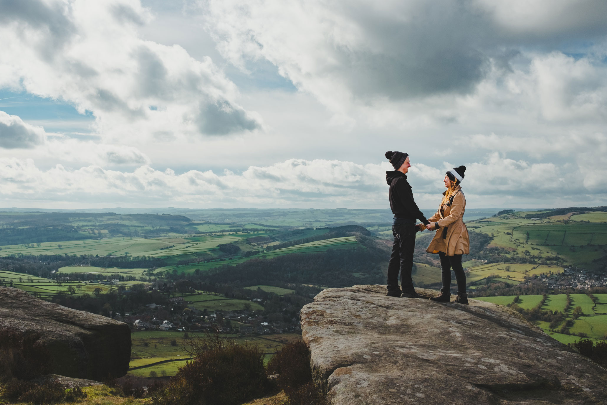 a couple hold hands as they look over dartmoor