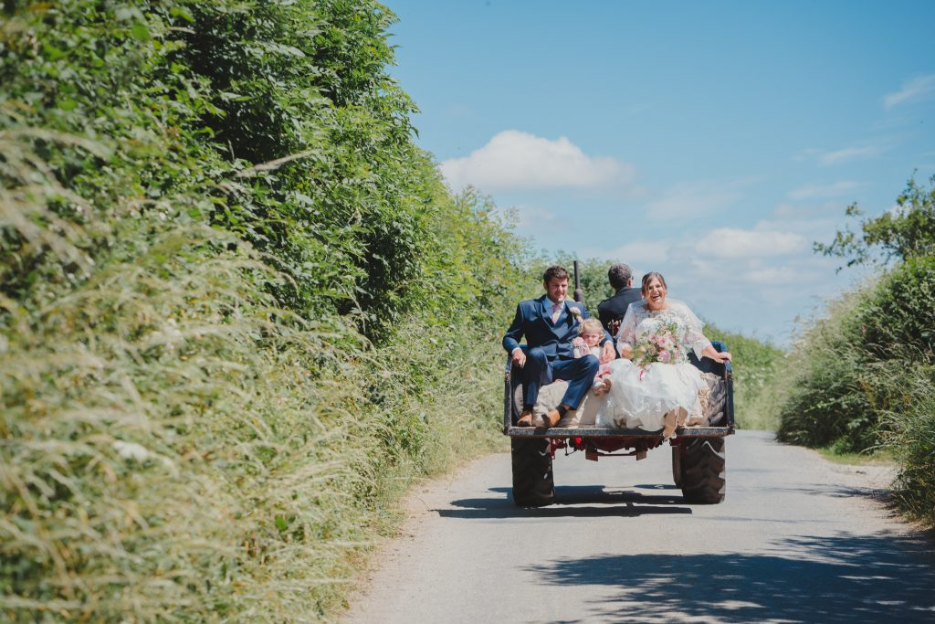 bride groom, pageboy and flower girl get taken to the wedding in the back of a tractor's trailer in the countryside]de