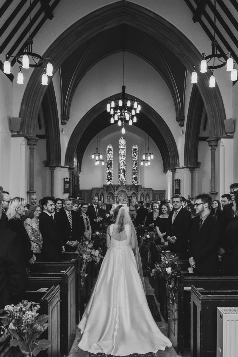 a bride gives herself away at a church wedding