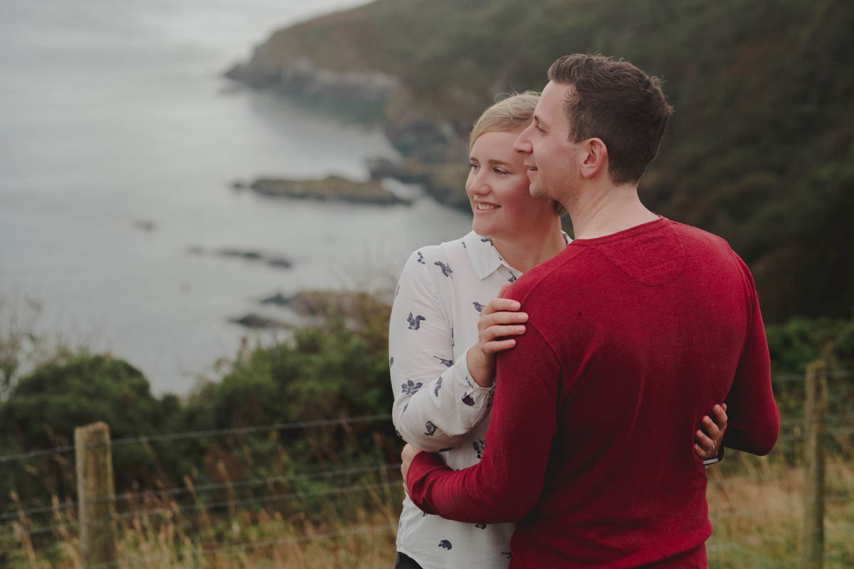 a couple look out over the Cornish coastline on their cornwall engagement shoot
