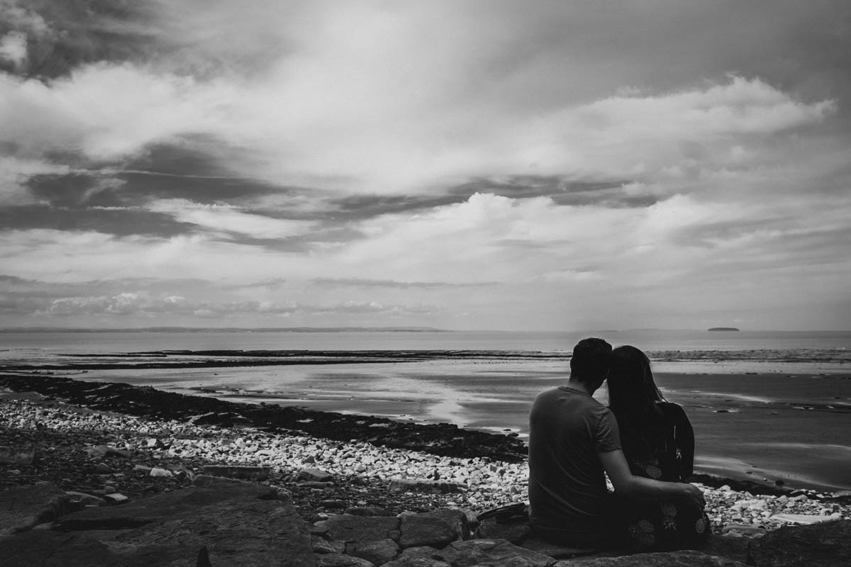 couple watch the sea on the beach near Exmoor on their pre-wedding shoot