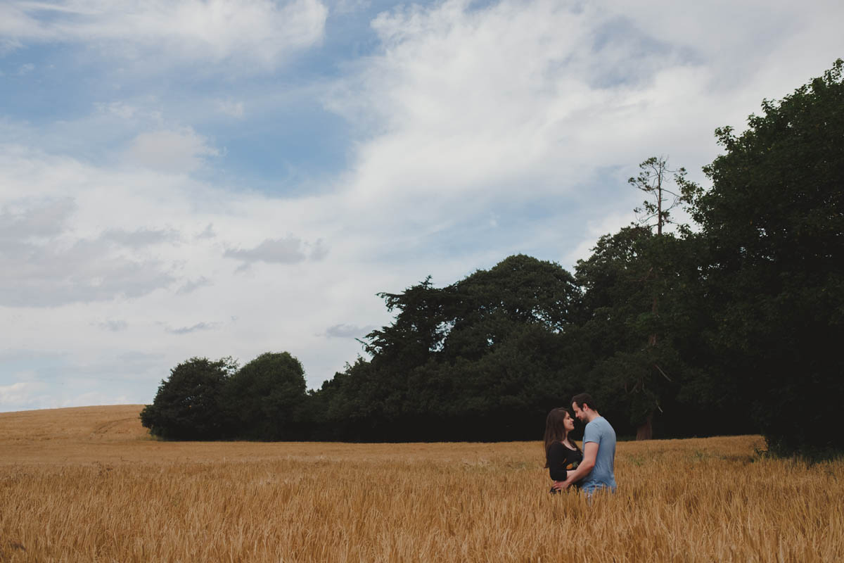 man and woman look into each other's eyes in a field of corn on their pre-wedding shoot