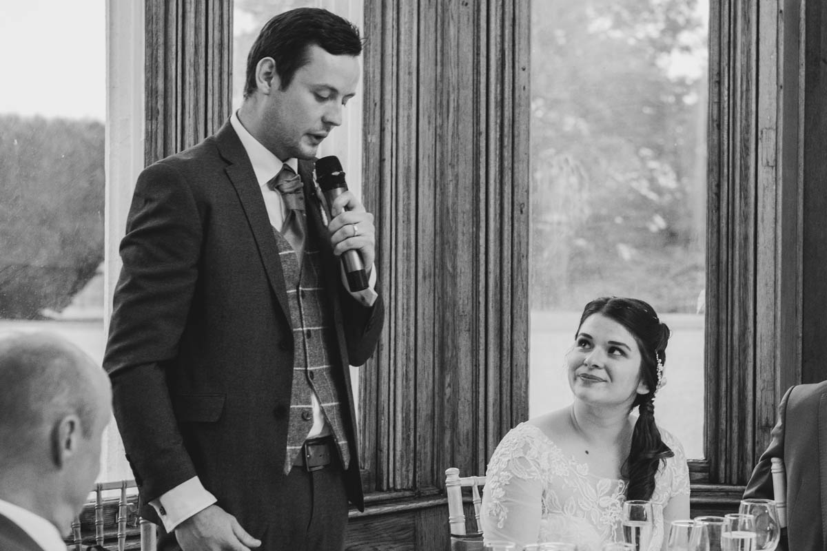 bride looks at her husband while he delivers his speech