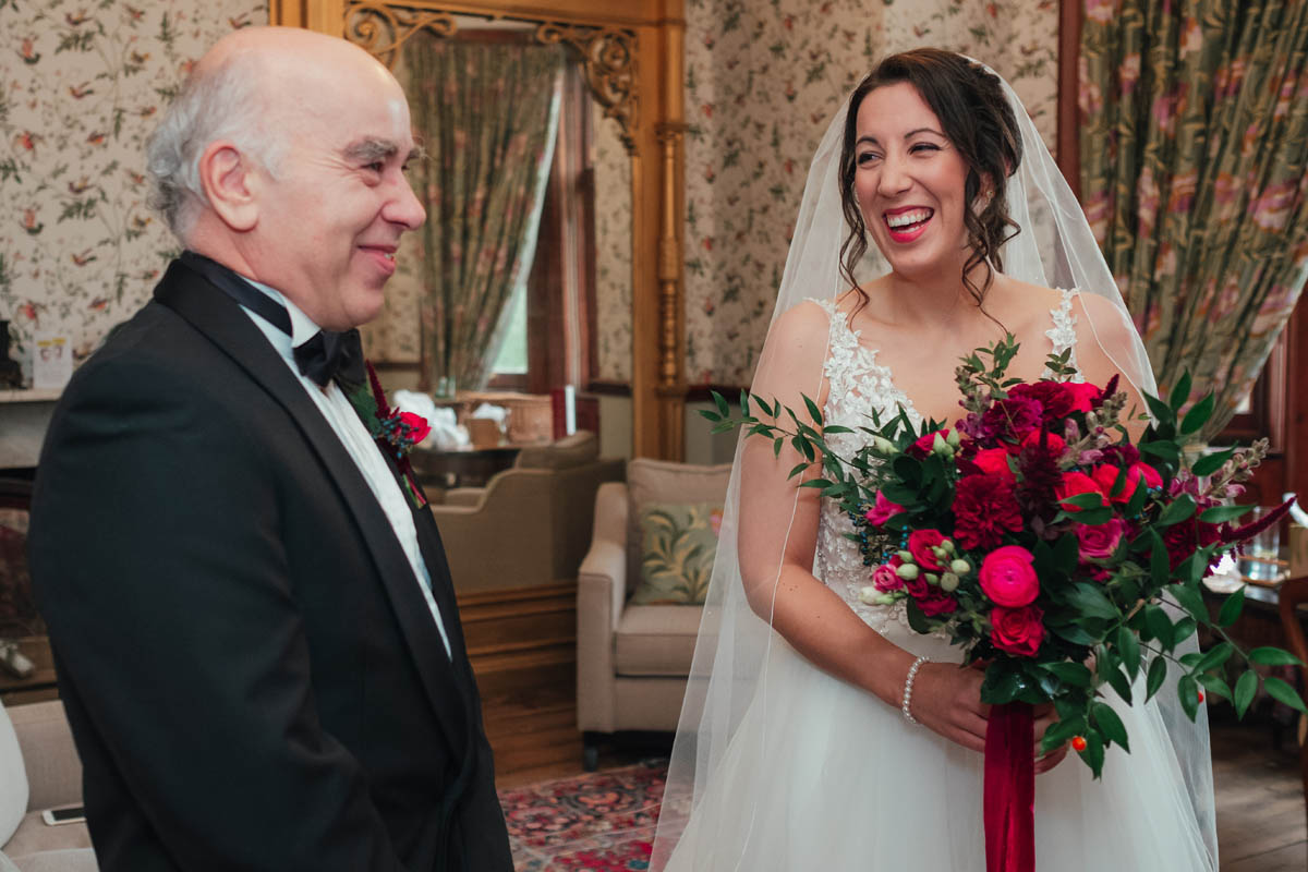 a bride and her dad laugh