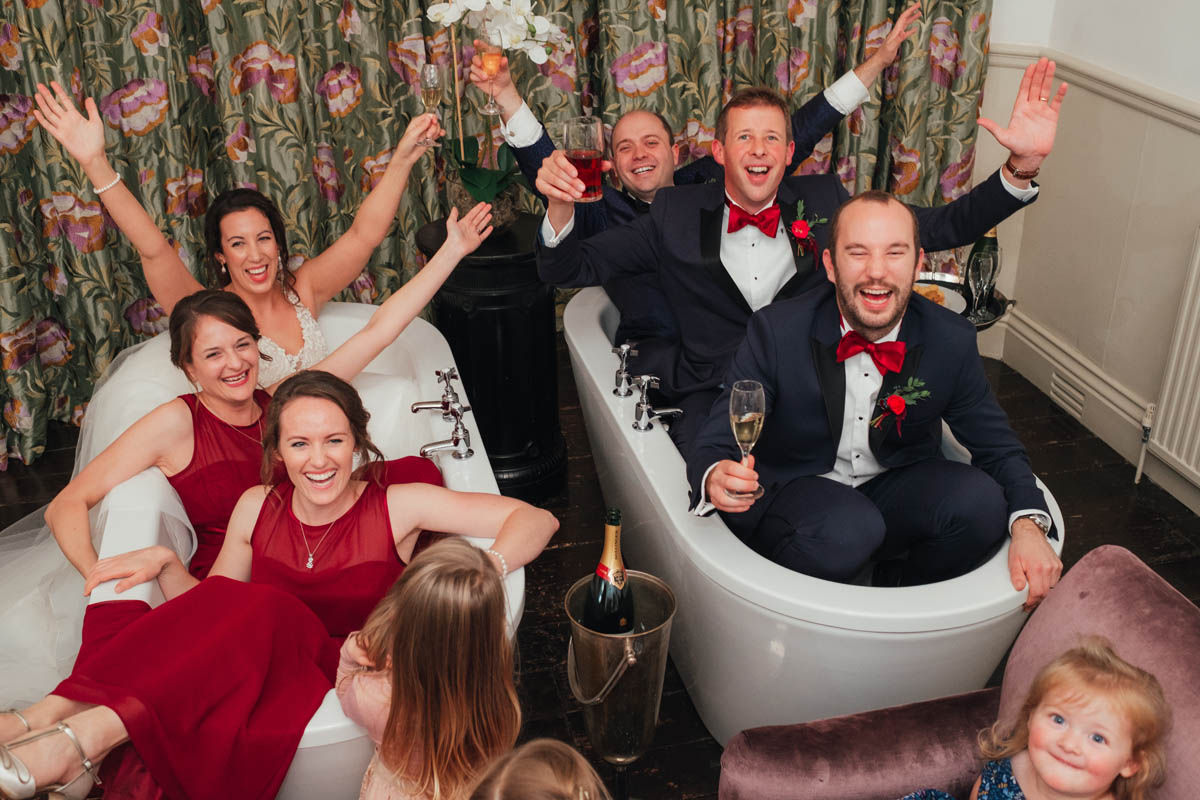 the bridal party lark about in the two enormous bath's at Huntsham Court's Bridal suite
