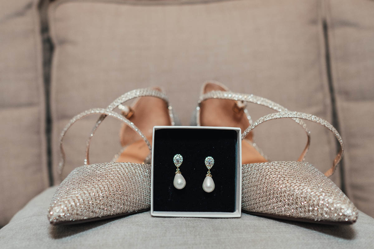 detailed shot of a bride's earrings and wedding shoes