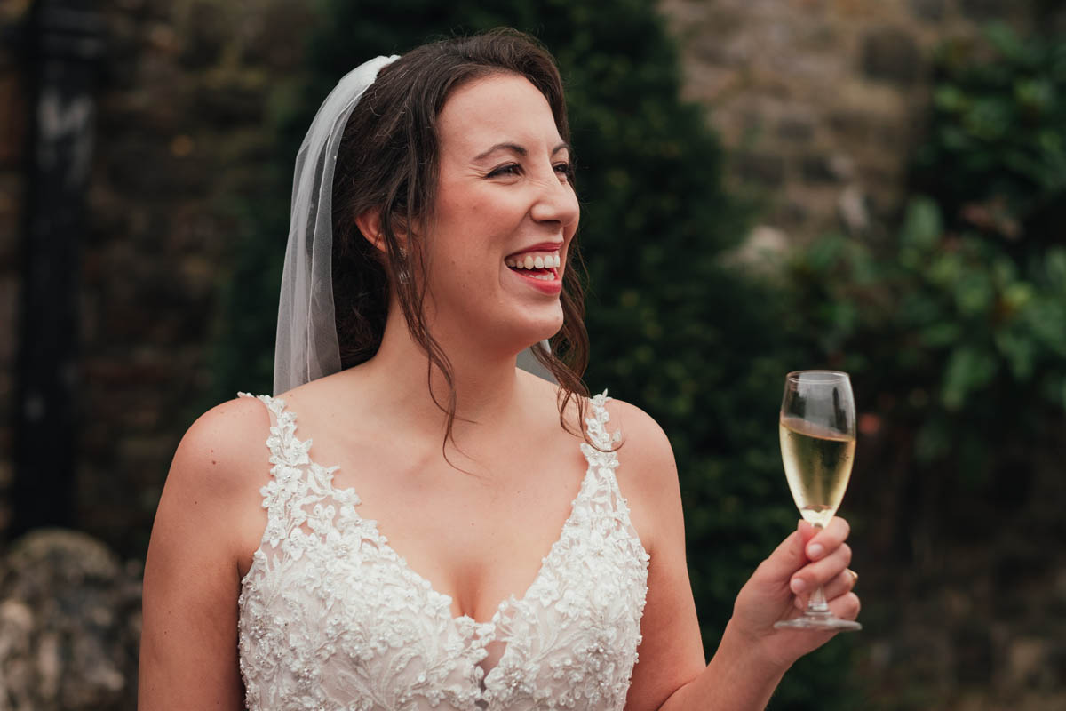 a bride smiles as she hols a glass of champagne at Huntsham Court