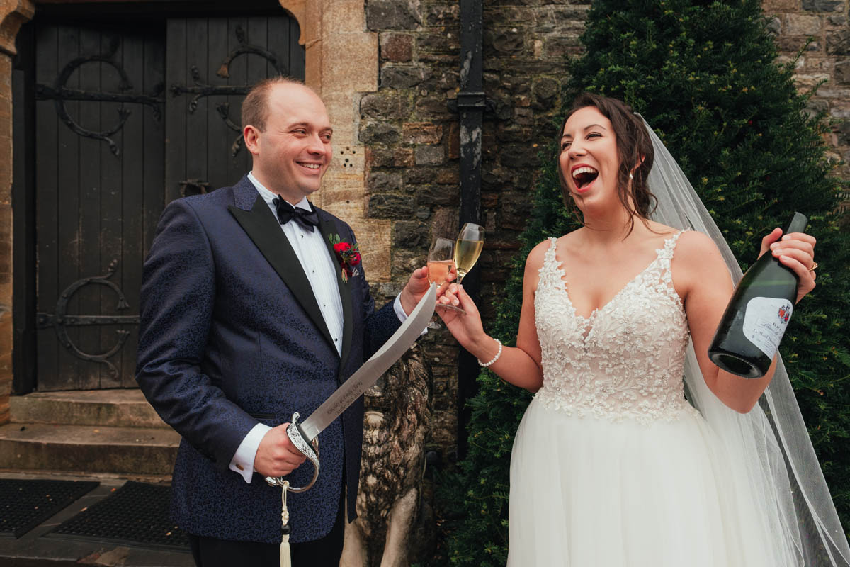 groom holds a sword while the bride laughs as she holds a bottle of champagne
