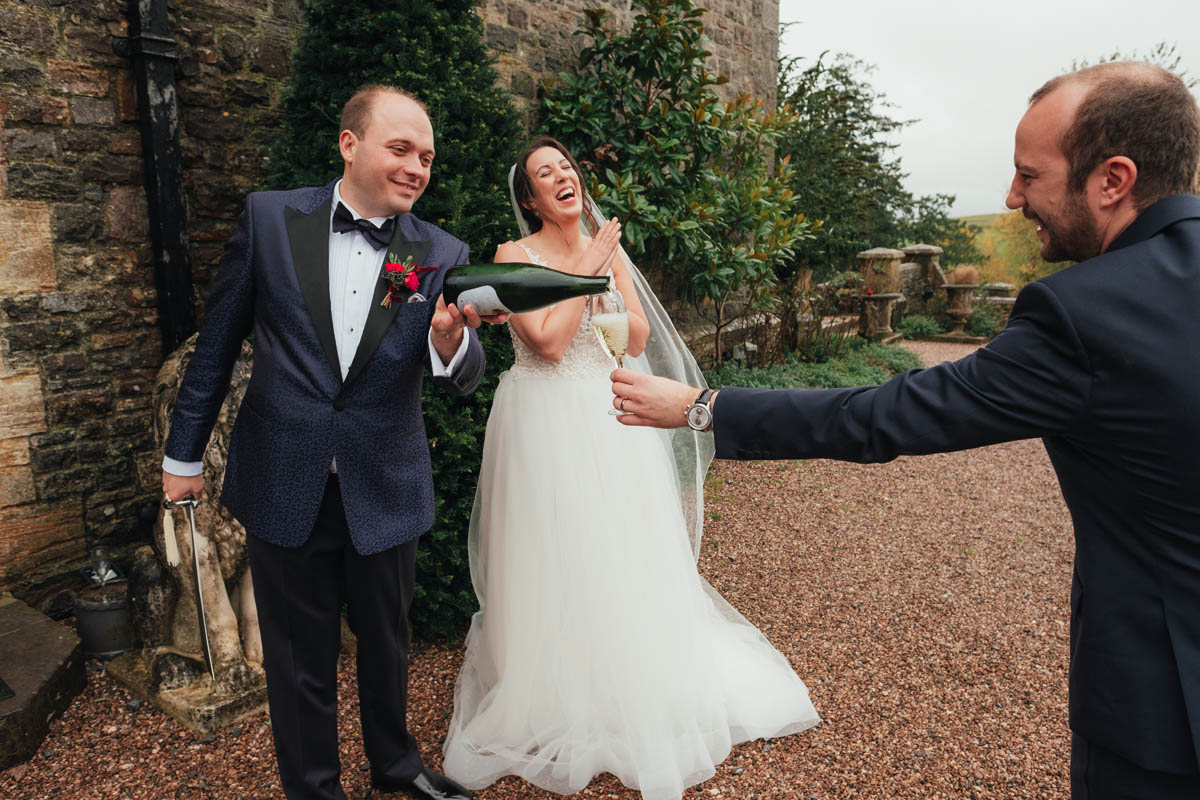 the groom pours champagne for guests