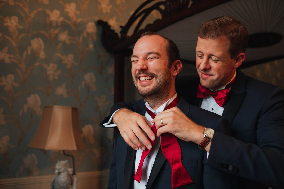 a best man helps groomsman do up his tie