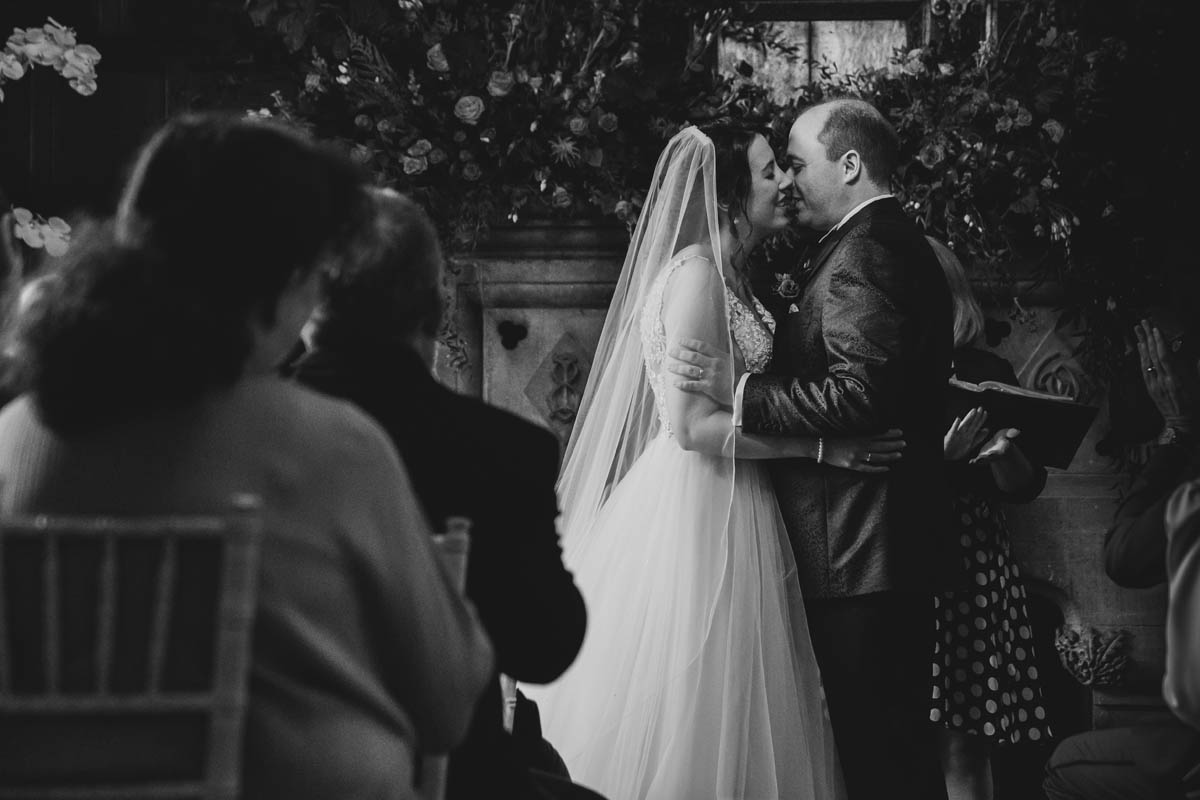 bride and groom share their first kiss at Huntsham's great hall