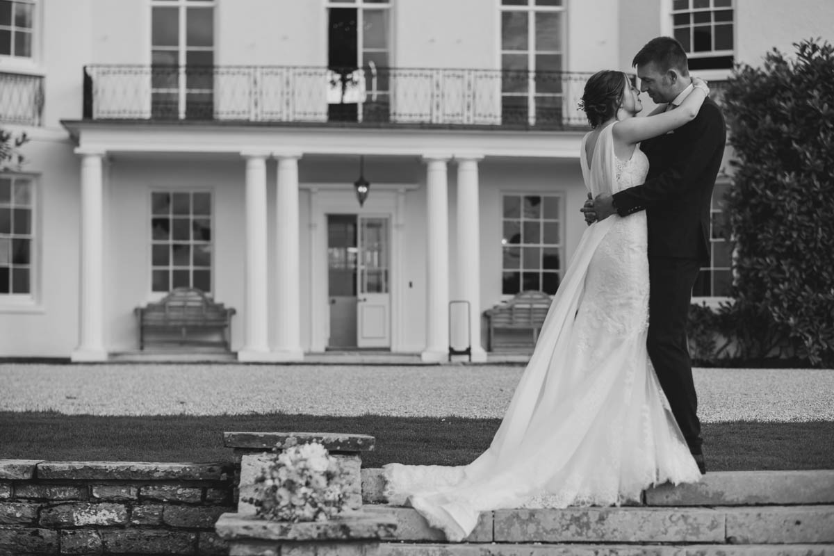 husband kisses his new wife outside Rockbeare Manor