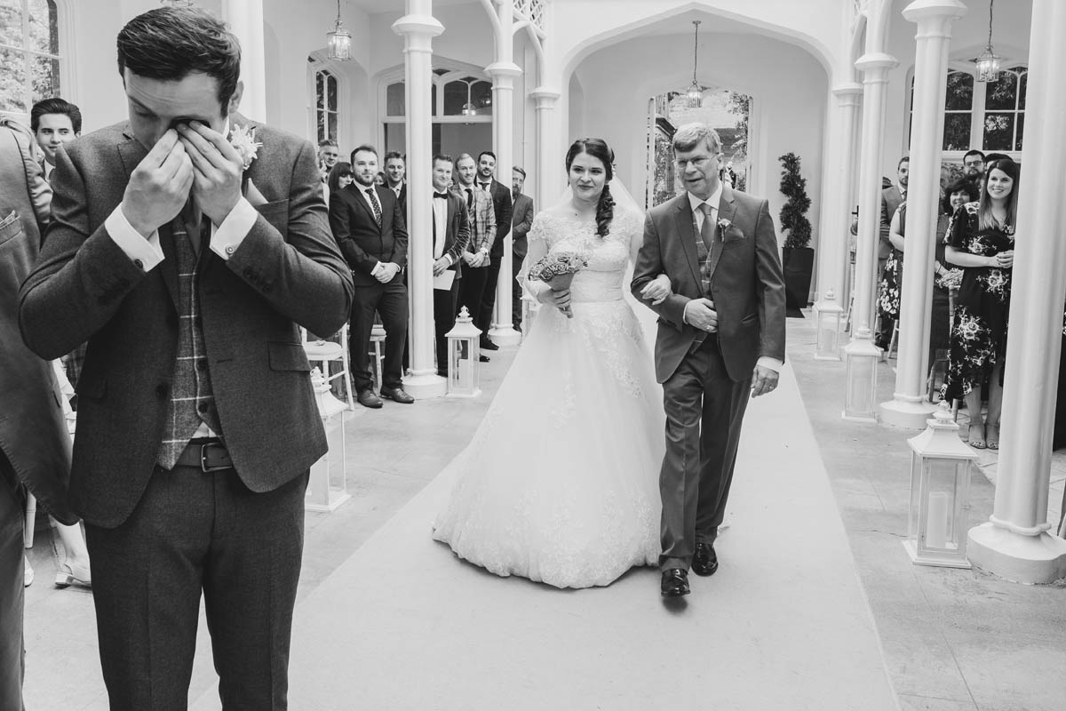 groom sheds a tear at the sight of his beautiful bride