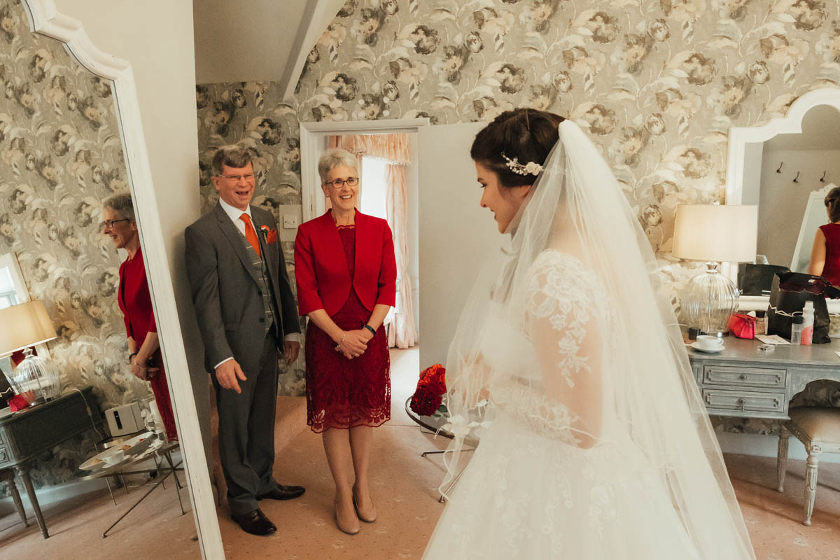 the bride's parents look delighted to see her