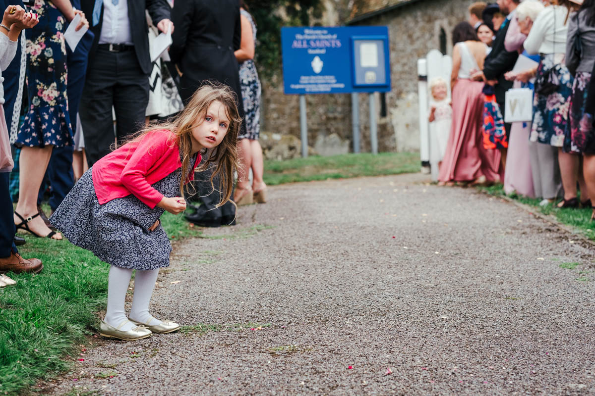 a little girl waits outside a church with a handful of confetti