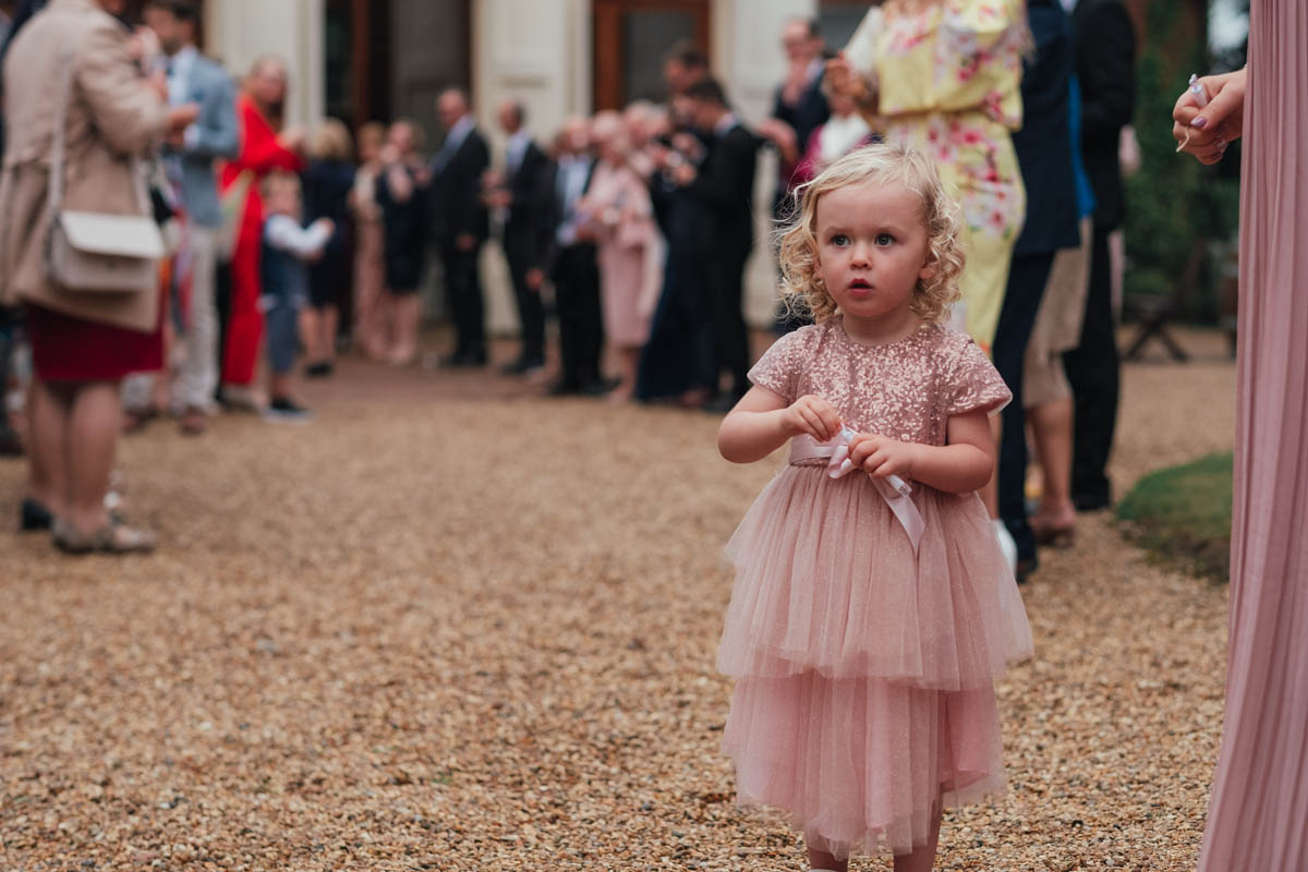 a little girl waits to blow bubbles over the bride and groom