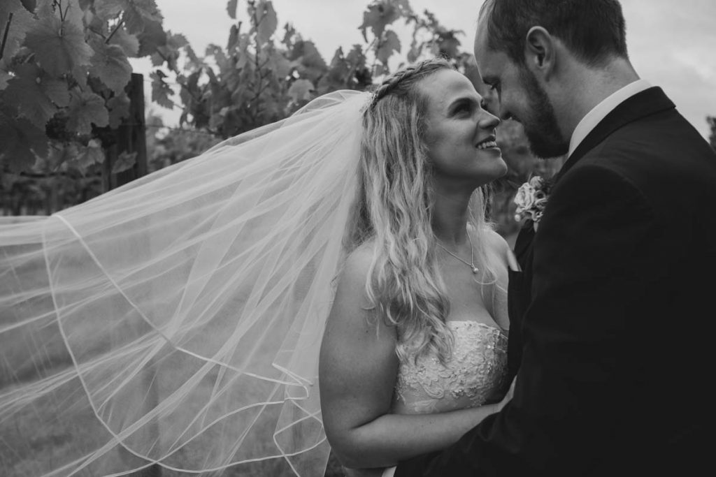 brides veil blows in the wind while she cuddles her groom