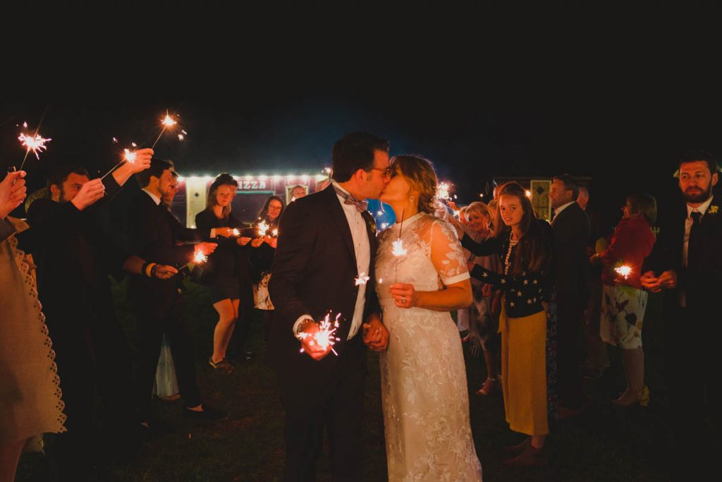a couple share a kiss whilst guests wave sparklers all around them on their wedding day