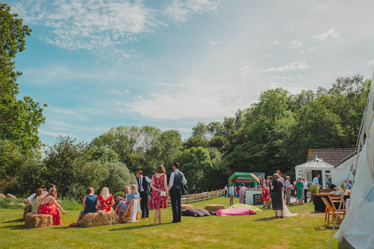 wedding guests relax outdoors at a festival themed wedding