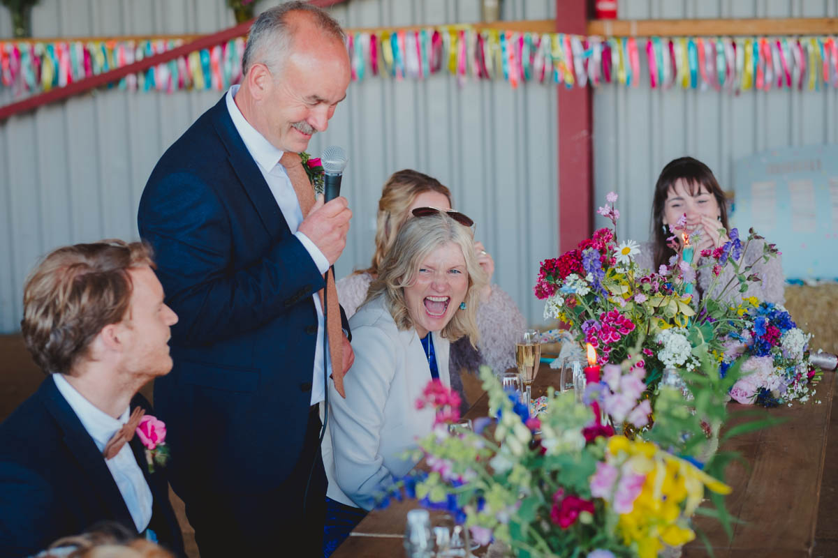 guests laugh at speeches at a Wiltshire farm wedding