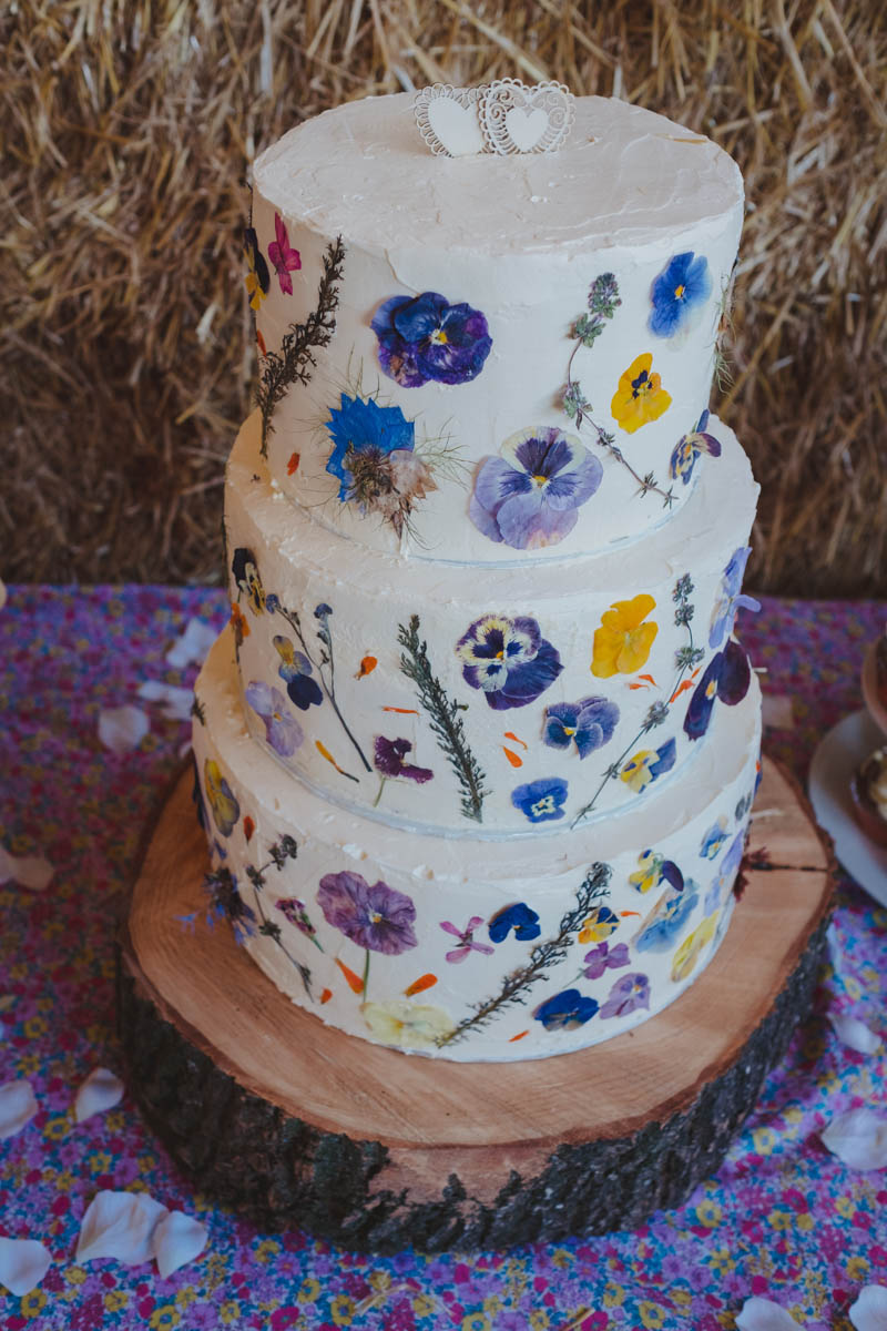 a wedding cake with pressed flowers as decorations