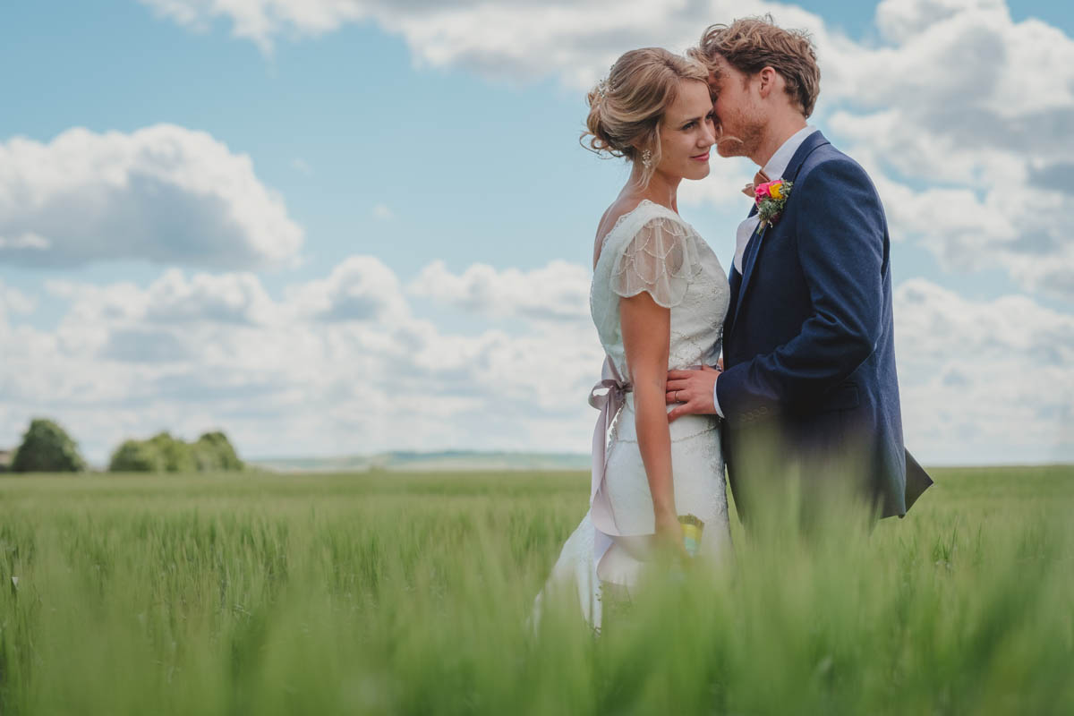 a bride and groom kiss in a field on a gorgeous summer's day