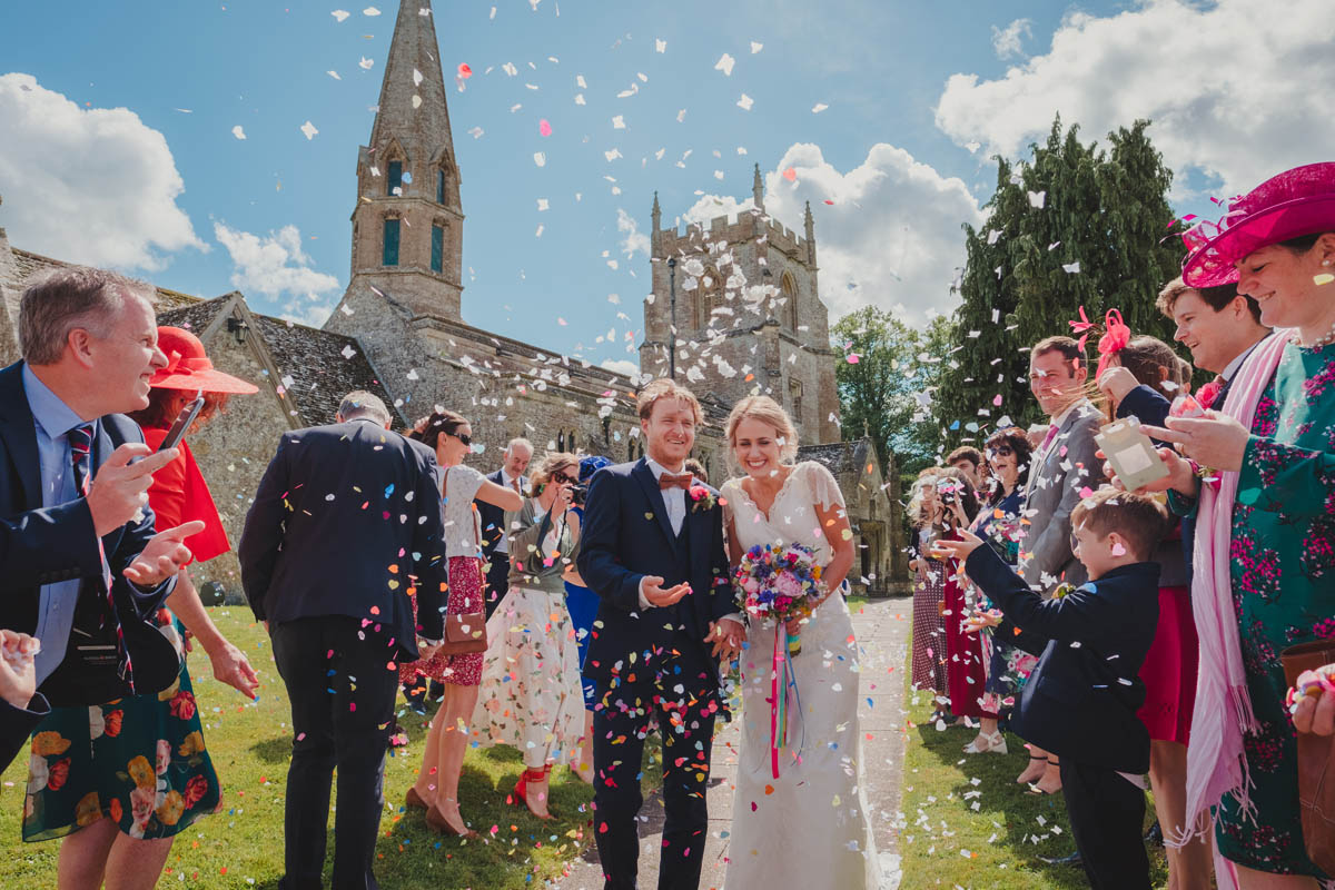 a newly married couple are welcomed into the churchyard by guests throwing confetti