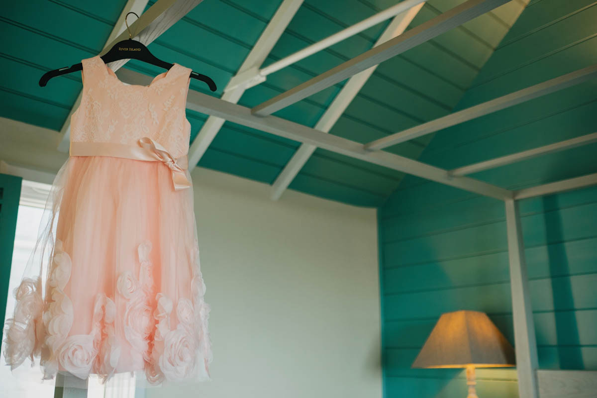 a bridesmaids dress hung up in front of a blue background