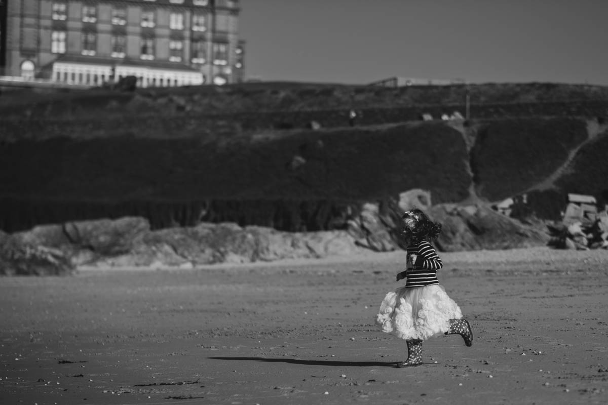 a bridesmaid runs along the beach at the Cornwall elopement