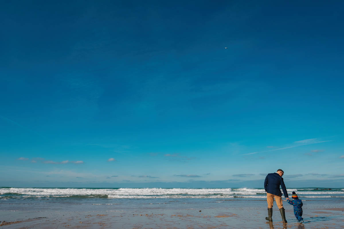 a son and his dad walk across Fistral beach, Cornwall
