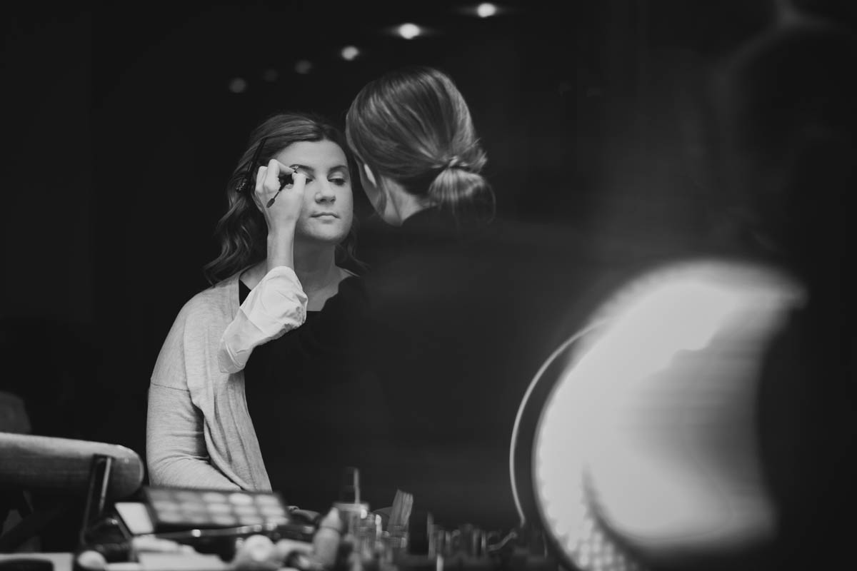 the bride has her make-up done in black and white