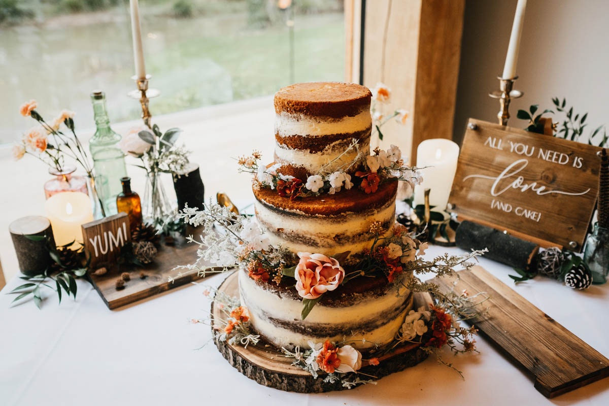 a naked wedding cake with silk flowers decorating it