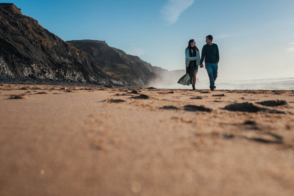 engaged couple walk hand in hand along charmouth beach