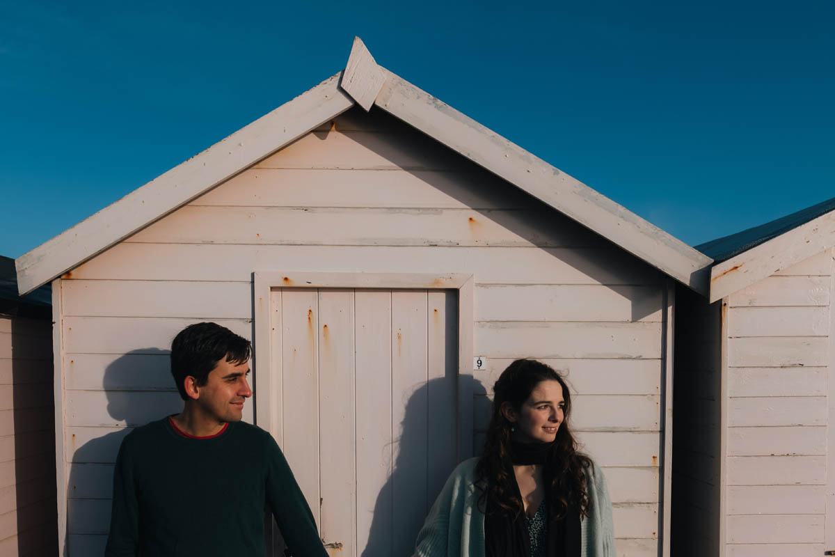 a couple look into the sun infront of a beach hut