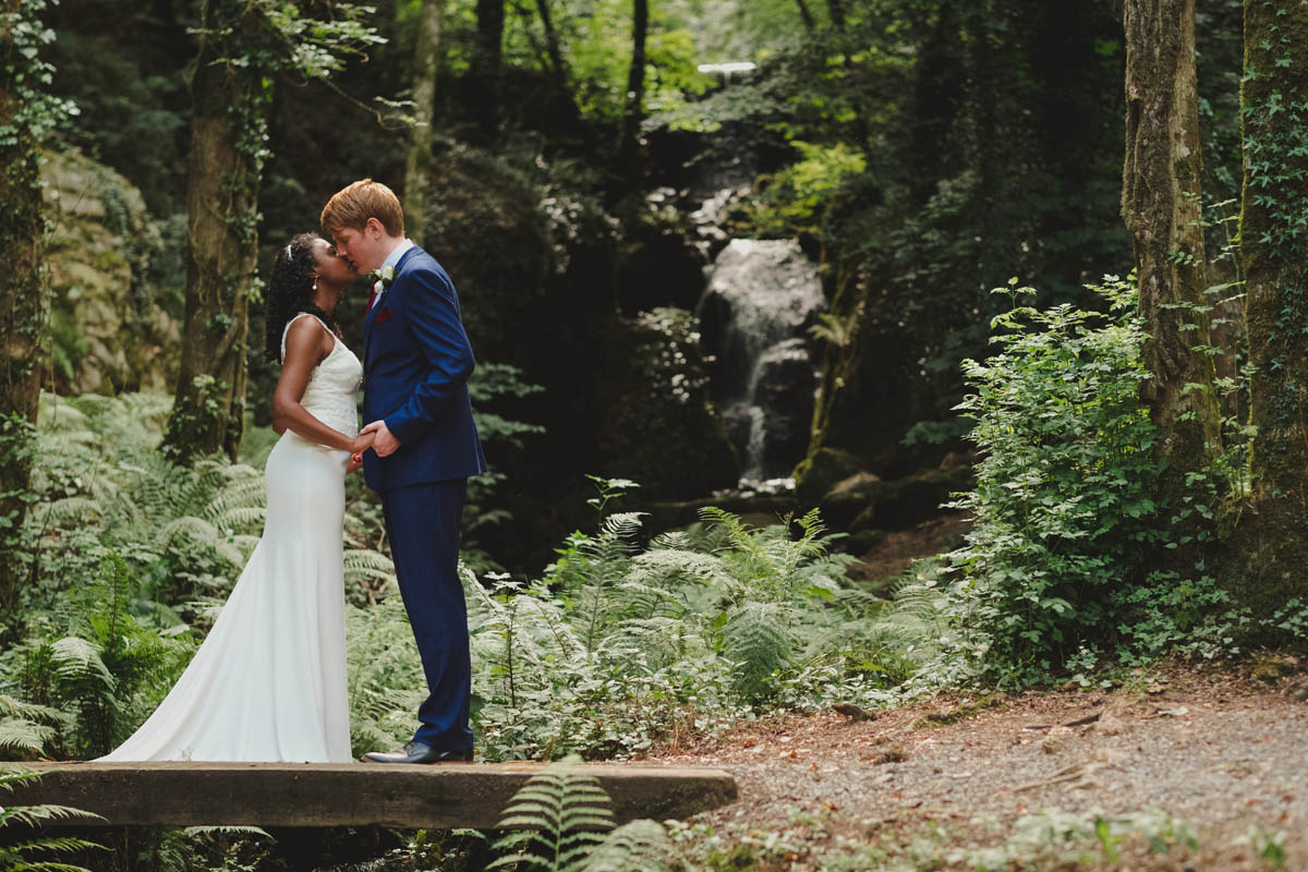 groom kisses his wife in front of the waterfall at canonteign