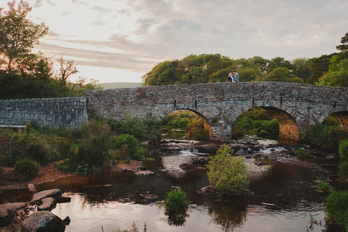 the bridge at postbridge with engaged couple on their pre-wedding shoot