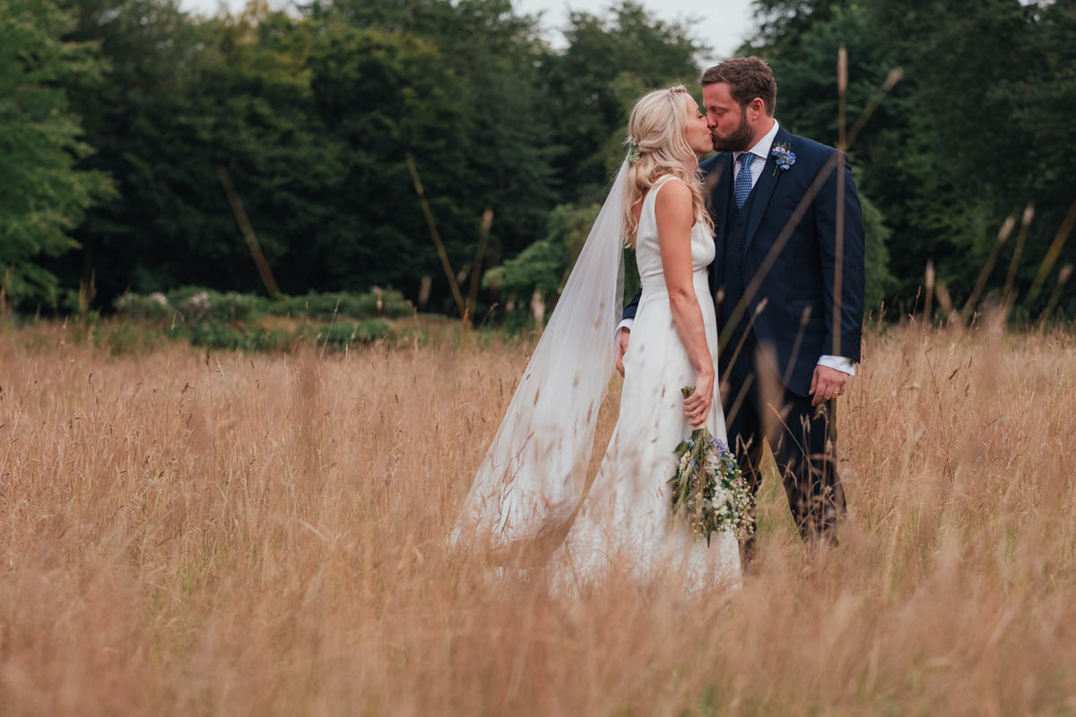 bride leans in to kiss her new husband in a golden field at their Bristol wedding