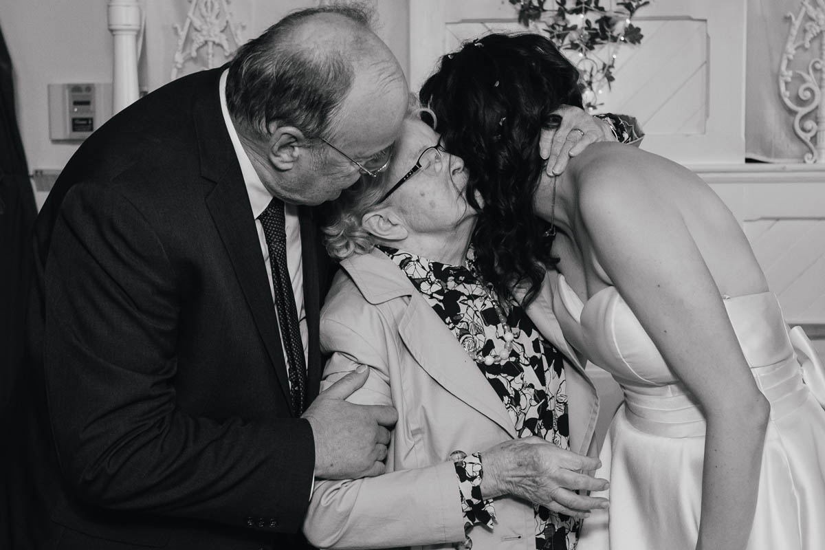 bride hugs her dad and her grandmother