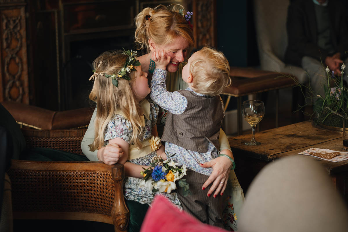 a wedding guest hugs her children