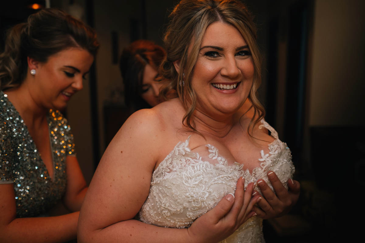 bridesmaids help her into her dress