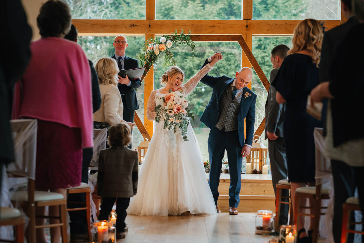 bride and groom throw their arms in the air in celebration of their marriage