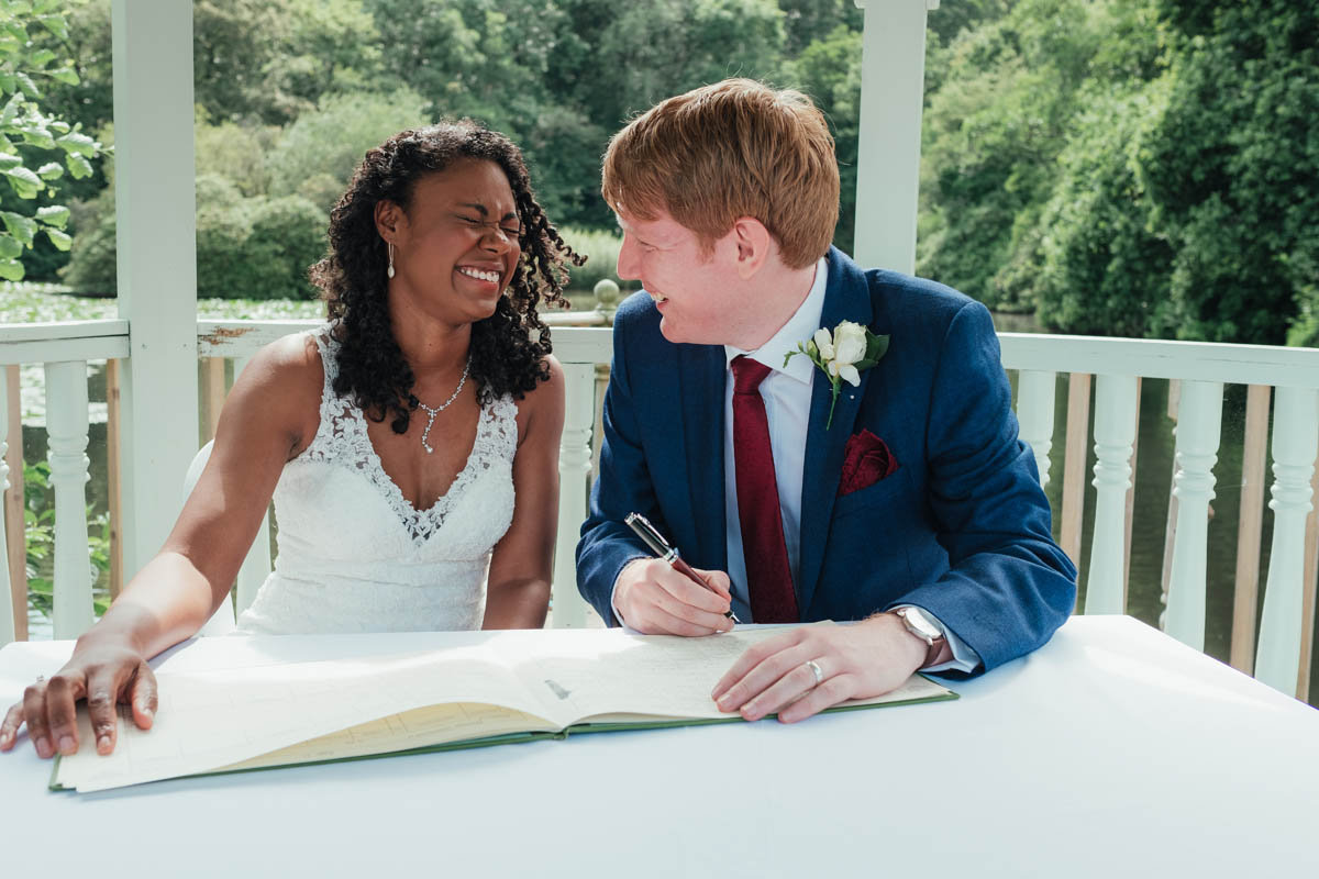 bride and groom laugh as they sign the marriage certificate