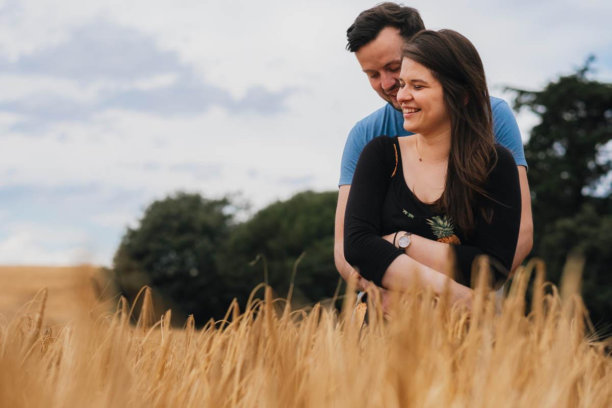 boy hugs his fiancée from behind in a field of corn
