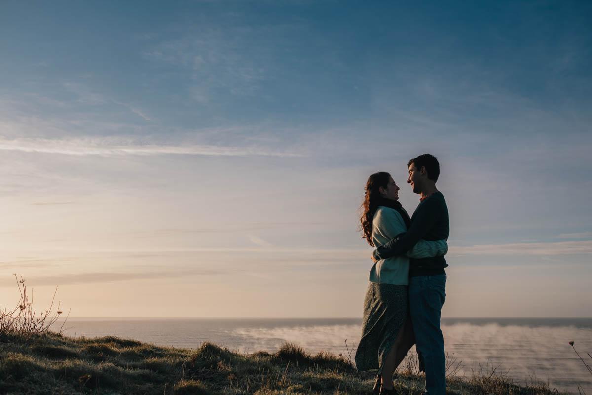 couple hug with seascape behind