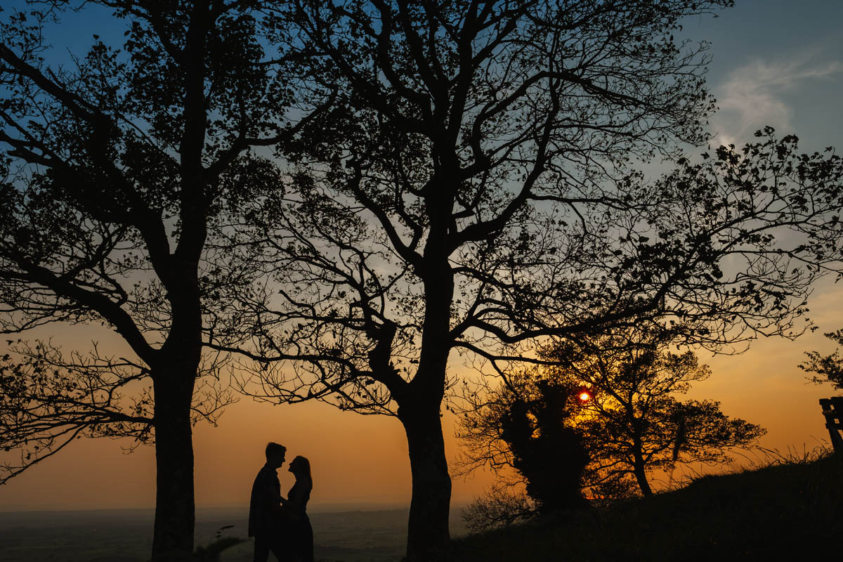 large oak trees and a couple kiss at sunset