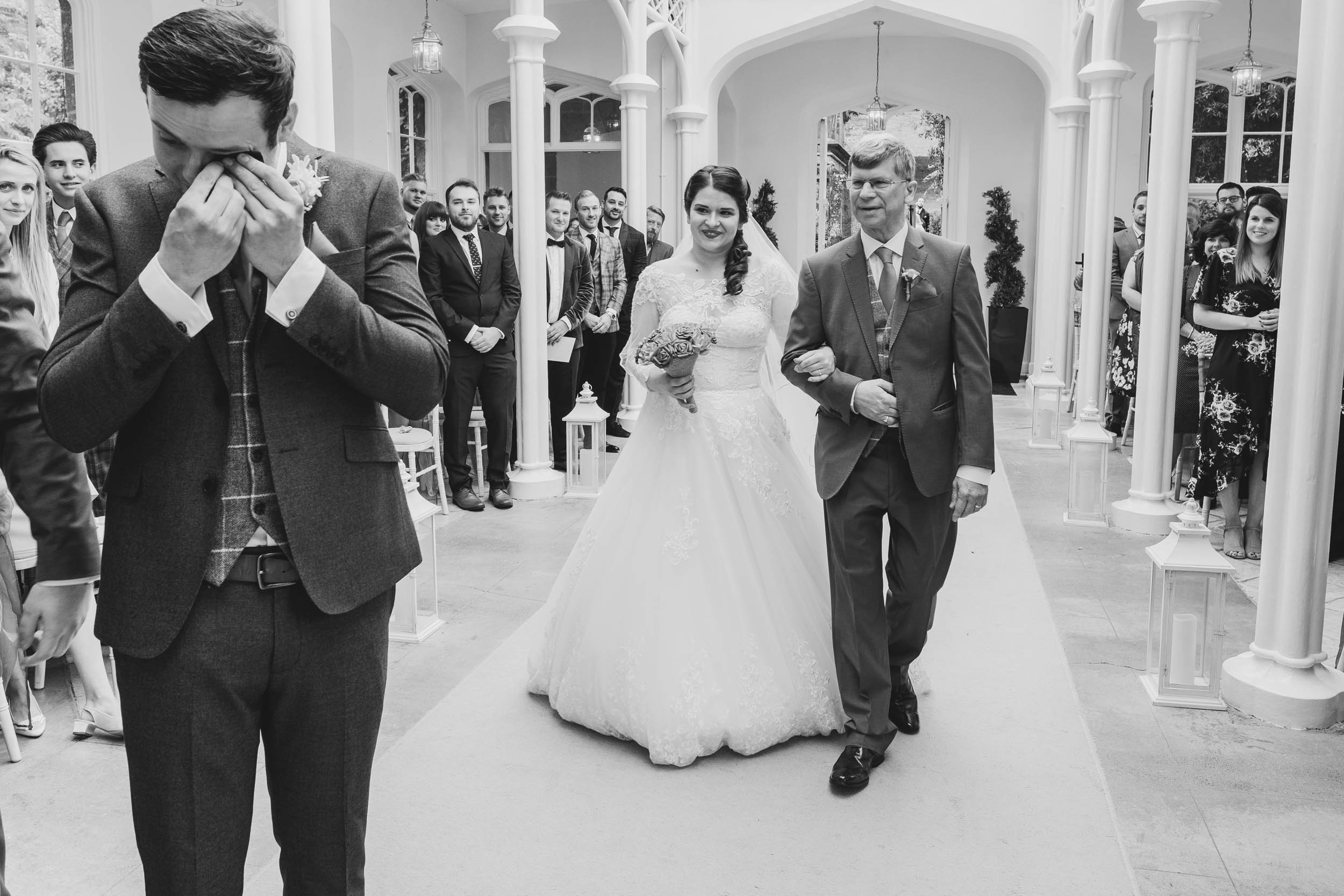 a groom cries at the sight of his bride walking down the aisle about to be given away by her father