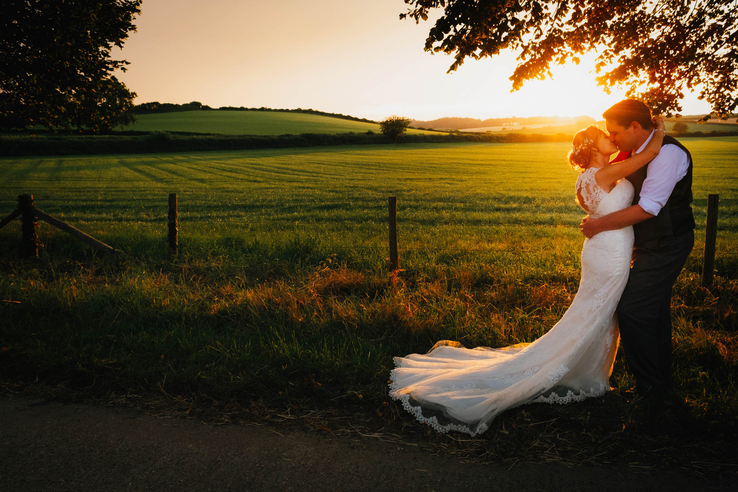 a photograph at a Bristol wedding where bride and groom kiss at golden hour