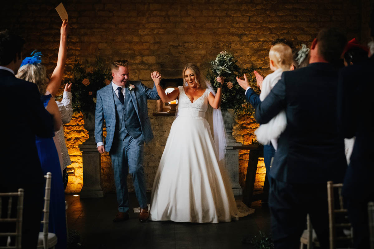 newly-married couple wave their hands in the air in celebration after the are pronounced husband and wife at their bristol wedding