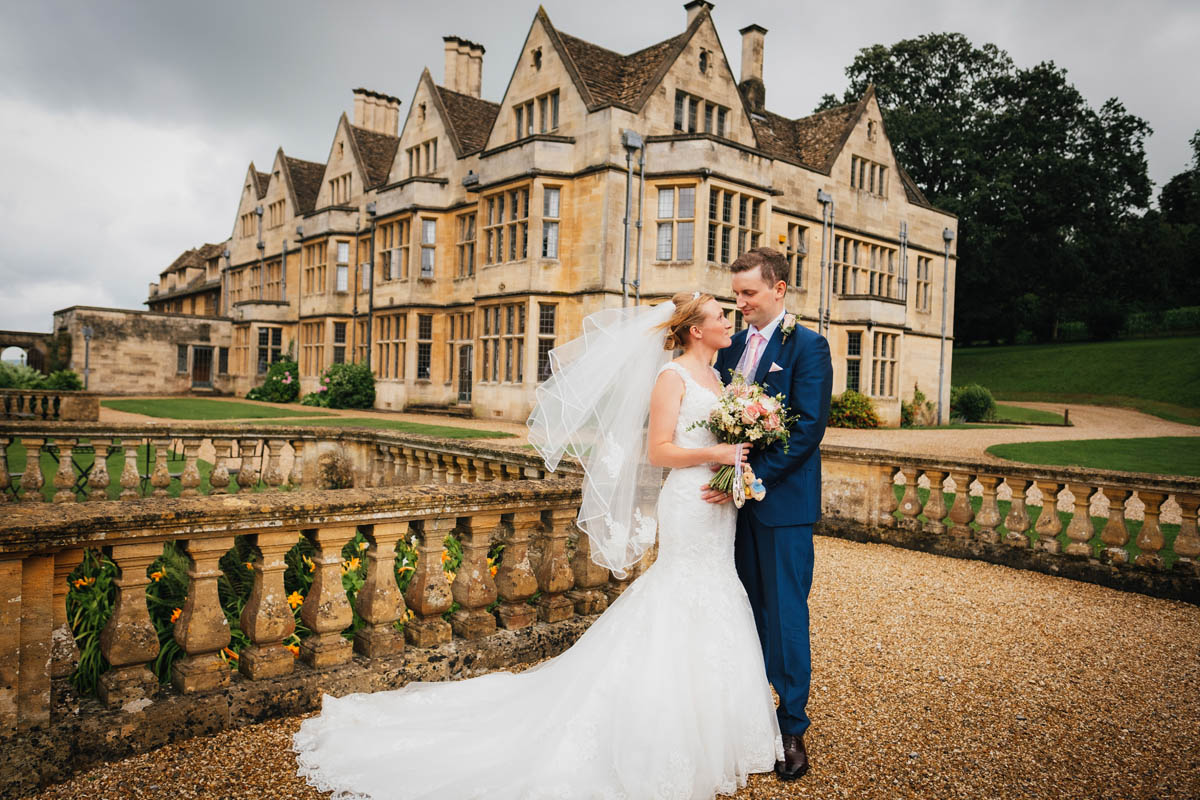 the bride's veil blows in the wind as she looks into her groom's eyes in front of Coombe lodge at Blagdon